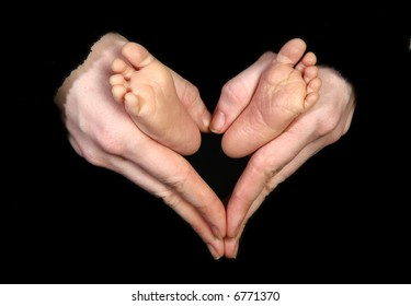 Baby feet held by mother's hands making heart shape.