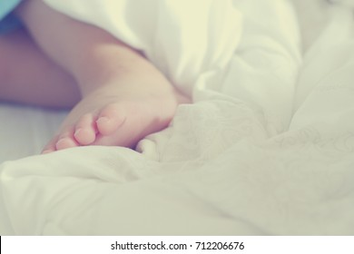 baby feet on bed close up