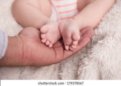 baby feet on father hands
