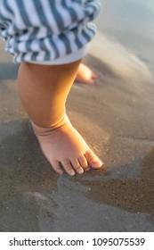 Baby feet on wet beach