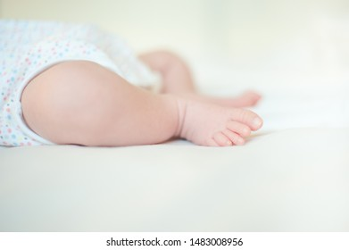 Baby feet on white bed