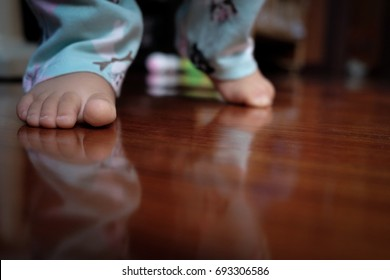 baby feet on a wood floor at first step of walking