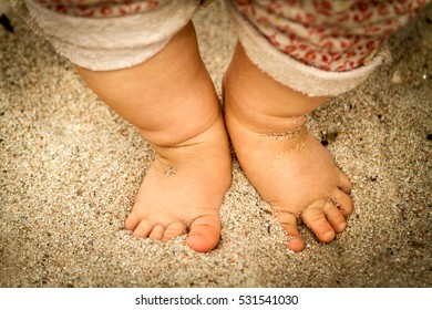 Baby feet in the sand.