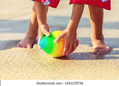 Baby feet walking on sand beach grabbing rugby ball – playful toddler wearing inflatable armbands hand holding ball from water in summer vacation - Children stand barefoot on sand