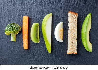 Baby finger food on black stone background, top view