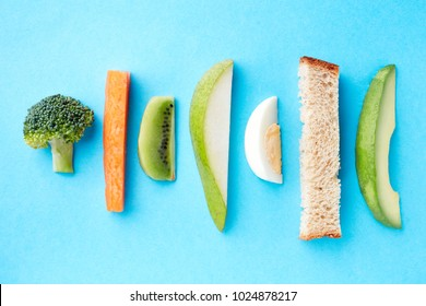 Baby finger food on blue background, top view