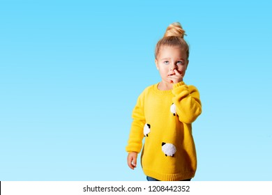 baby with finger in nose. cute girl of three years old intently picking at her nostril and looking at the camera. hygiene. blue background - Image