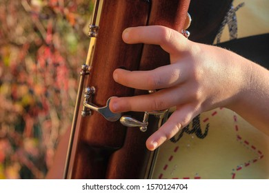 Baby fingers on bassoon buttons. Fragment. Wooden musical instrument. Close up.