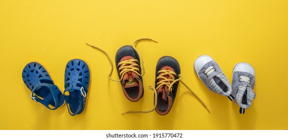 Baby first steps. Three pairs of boy blue shoes variety on yellow color background, top view. Kids footwear, beach sandals, booties and soft infant shoes in a row.