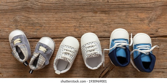Baby first steps. Three pairs of boy shoes variety on wood floor background, top view. Kids footwear, booties and soft infant shoes in a row.