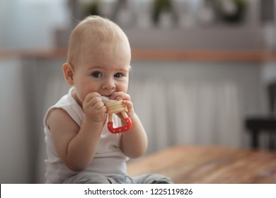 Baby first teeth gnaws fruit in a safe device, the concept of safe first lure, healthy food