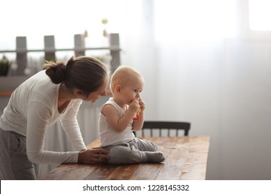 Baby first teeth gnaws fruit in a safe device with mother, the concept of safe first lure, healthy food