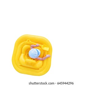 Baby floats in a yellow inflatable raft isolated on a white background. Small child with a shovel in yellow rubber ring, view from the top. Background with copy space.