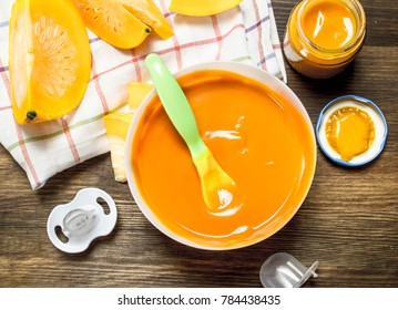 Baby food. Baby puree from fresh pumpkin. On a wooden table.