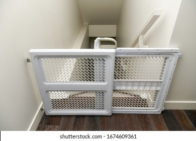 Baby gate at top of steep staircase