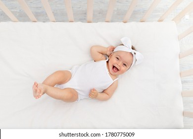 baby girl 6 months old lies in a crib in the nursery with white clothes on her back and laughs, looks at the camera, baby's morning, baby products concept