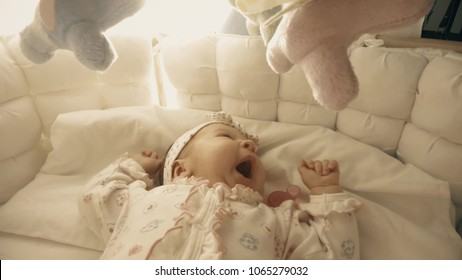 Baby girl about to sleep in her cot