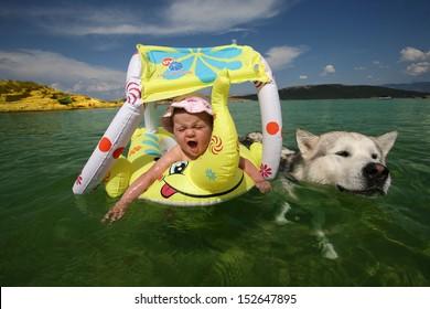 Baby girl and Alaskan malamute dog playing in sea