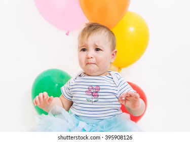 Baby girl with balloons crying