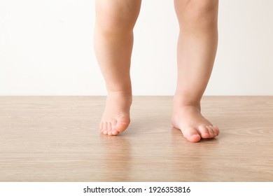 Baby girl barefoot on wooden floor background. Closeup. First steps. Front view.