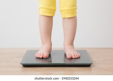 Baby girl with barefoot standing on weight scales on wooden floor at light gray wall background. Closeup. Front view. Care about body. Weight control concept.