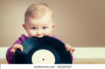 A baby girl bite a vintage vinyl record with empty mockup label