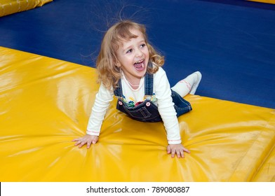 baby girl with blond hair, in blue overalls fun run and jump on a trampoline