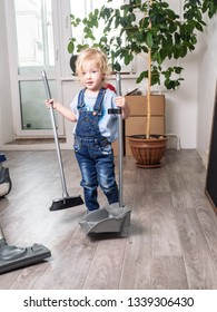 Baby girl in blue denim overalls is cleaning the house and sweeping the floor with a broom.