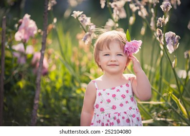 baby girl with blue eyes blond hair and pink peony in her hair in summer garden with bright flowers.  She dressed on white with floral pattern summer dress.