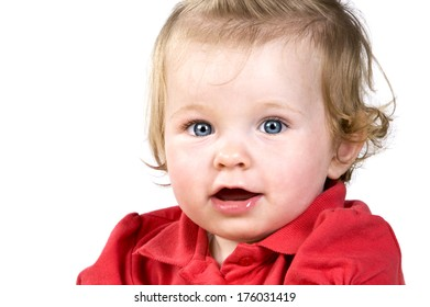 Baby girl with blue eyes and a red shirt.
