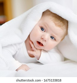 Baby girl with blue eyes wearing white towel or blanket in white sunny bedroom. Newborn child relaxing in bed. Nursery for children. Textile and bedding for kids. Happy cute new born girl or boy.