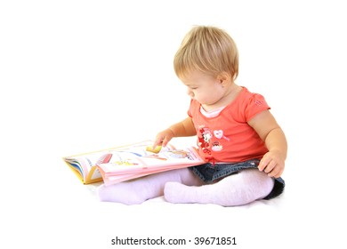Baby girl with book sitting on white blanket