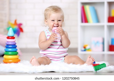 Baby girl with bottle sitting on white carpet