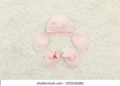 Baby girl and baby boy bodysuit, socks, gloves and hat on light wooden table. Top view, Mock up