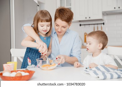 Baby girl breaks egg for dough into flour under direction of the mother, younger brother sits beside white table and helps. Concept of friendly family cooks cakes for Easter.