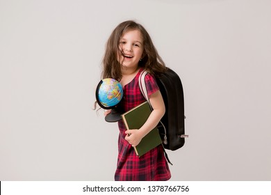 baby girl brunette in school dress with books briefcase and globe on white background,back to school
