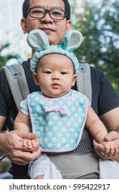 baby girl in a baby carrier with father, outdoors portrait
