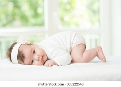 Baby girl child lying down on white blanket
