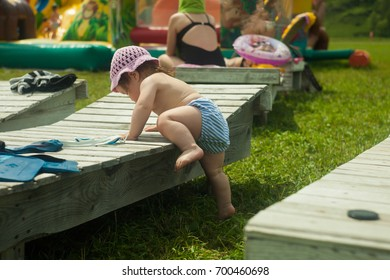Baby girl climbing up the wooden bench in the park