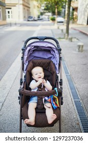 Baby girl with colorful toys in stroller. Little child in pram. Infant kid outdoors in pushchair