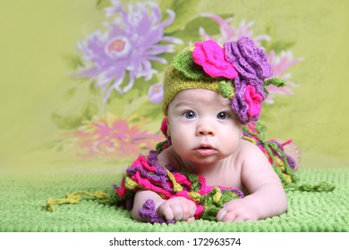 baby girl in a coquettish hat with flowers