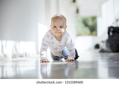 Baby girl crawling along open passage in house