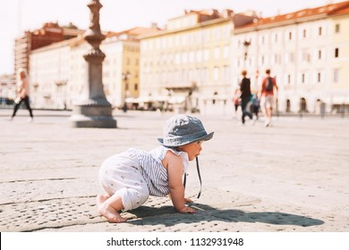 Baby girl crawling on a european city street in Trieste, Italy, Europe. Little child outdoors in a town.