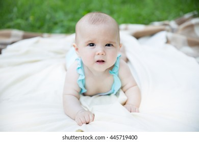 Baby girl crawling outdoor. Selective focus on her eyes.