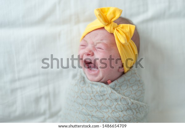Baby girl crying on bed