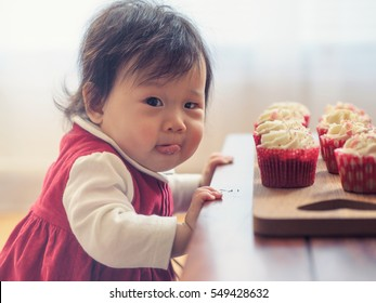 Baby girl with cup cake at home party