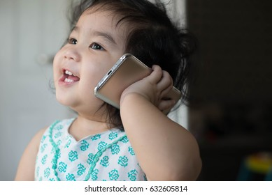 Baby girl  cury hair 1 year with smart phone calling and happy smile.