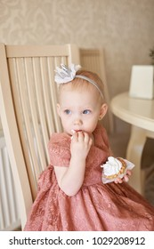 Baby girl in a cute pink dress sitting next to the kitchen table and having tea time. Alice in Wonderland party theme. Child's. birthday party. Cake smash. Kid eating cupcake. Light beige background