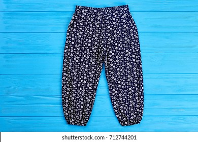 Baby girl dark blue pants. Fashionable pants for baby girl on blue wooden background. Kids fashion harems.