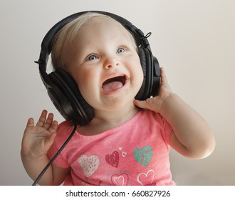 Baby girl does not like the music she's listening to through headphones